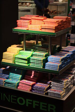 Amsterdam Schiphol Airport, the Netherlands - september 24th 2019: Tony Chocolonely chocolate, a Dutch fairtrade brand. Promotional display in airport shopping area. Various colors representing different flavors.