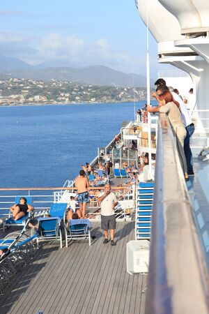 Savona, Italy - September, 26th 2019: Costa Magica, passengers enjoying the fresh air on the ships top deck. Leaving Savona cruise terminal