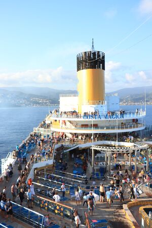 Savona, Italy - September, 26th 2019: Costa Magica, passengers on the ships pool deck while leaving Savona cruise terminal