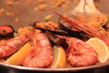 Big prawns or gambas, pieces of lemon and mussel in a traditionl paella pan. Close up