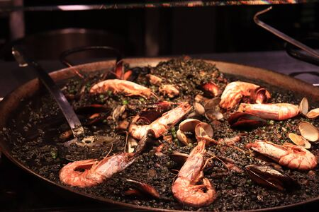 Arros negre or black paella, a traditional Catalan seafood dish with gambas and mussels