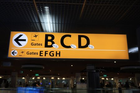 Amsterdam, the Netherlands - september 24th 2019: Yellow illuminated sign at airport with gate letters for departing flights at Amsterdam International Airport Schiphol Editorial
