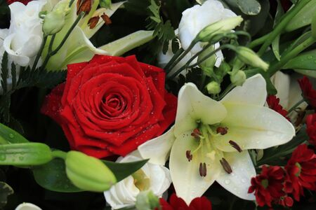 Red roses and white lilies in a big wedding centerpiece Foto de archivo