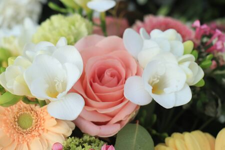 Mixed yellow pink flower arrangement: various flowers in different shades of yellow and pink for a wedding