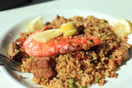 Plate with traditionale Spanish paella with a big gamba and slices of lemon