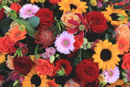 Mixed wedding flower arrangement: big yellow sunflowers with red roses and other flowers in orange and pink