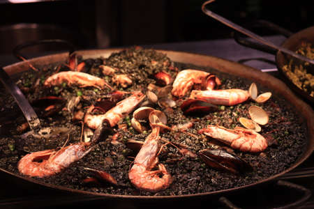 Arros negre or black paella, a traditional Catalan seafood dish with gambas and mussels Stockfoto