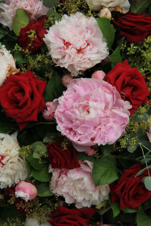 Red roses and pink peonies in a wedding arrangement