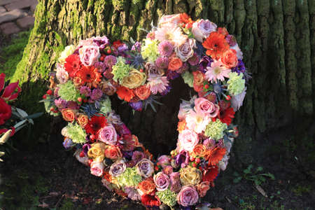 Heart shaped sympathy flowers: roses and gerberas in various colors