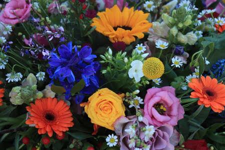 Colorful bridal flower arrangement: orange gerberas, yellow roses, sunflowers and lisianthus Standard-Bild