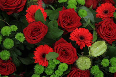 Green red flower arrangement: big red roses and green Standard-Bild