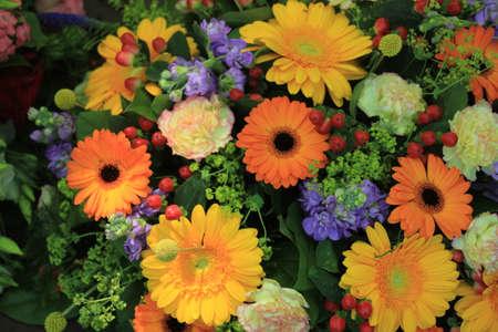A mixed flower arrangement with yellow and orange gerbers Standard-Bild