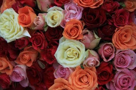 Variation of orange, red and pink roses in a wedding flower arrangement