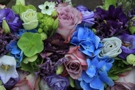 Blue hydragea and purple roses in a blue purple wedding bouquet and centerpieces
