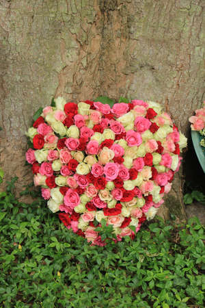 Heart shaped sympathy flowers near a tree at a cemetery