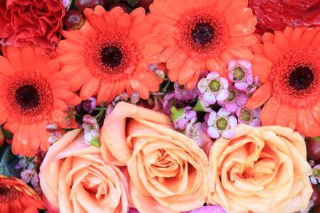 Pink and orangeflowers in a big wedding centerpiece, roses and gerberas