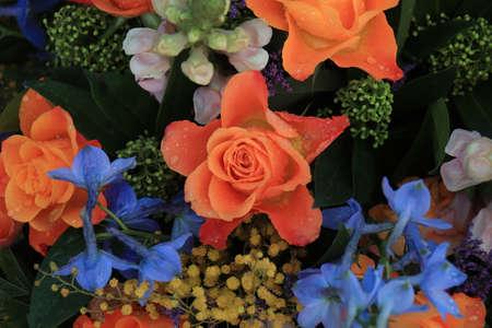 Orange and blue flower arrangement for a wedding: orange roses and blue larkspur