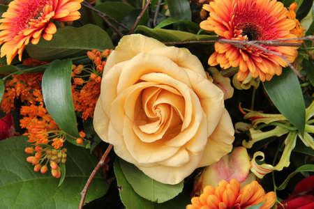 Yellow orange rose in a mixed flower arrangement Standard-Bild