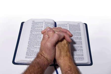 personas orando: Manos de rogaci�n en la biblia Foto de archivo