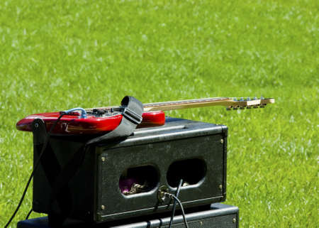 tremolo: red electric guitar and combo amplifier on the grass