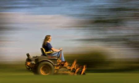 tondeuse: tonte de pelouse avec le flou de mouvement indiquant la vitesse