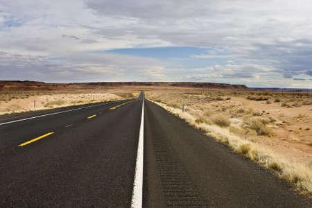 Desert wilderness road leading to bluffs photo