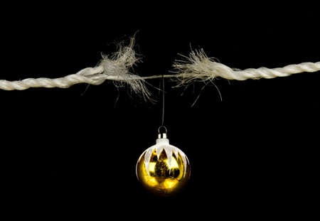 unwinding: Frayed rope with christmas bulb holiday stress concept isolated on black background  Stock Photo
