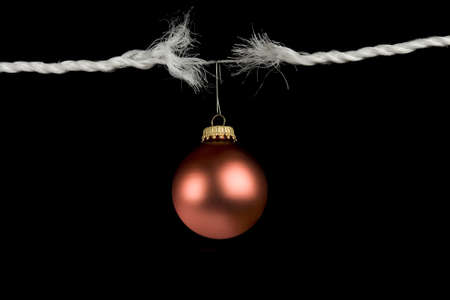 risk of war: Frayed rope with christmas bulb holiday stress concept isolated on black background  Stock Photo