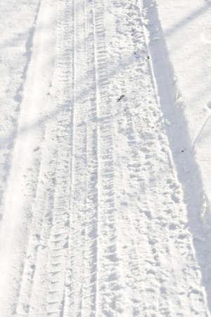 Sporen van een zwaar voertuig in witte sneeuw Stockfoto