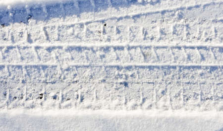 Tracks of a heavy vehicle in white snow photo