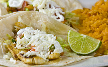 Healthy mexican meal, fish tacos vegetables and rice on plate  photo