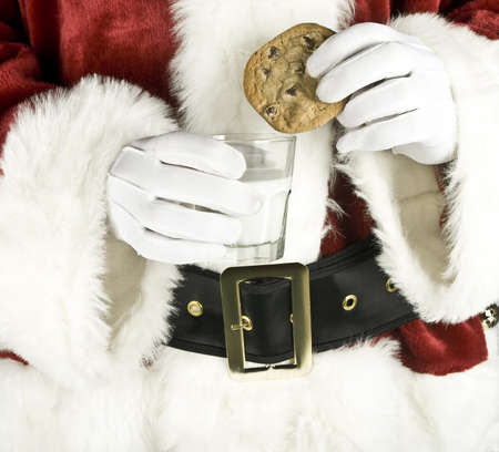 Santa Claus Hand holding milk with a chocolate chip cookie