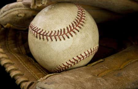 guante de beisbol: Una pelota de béisbol en un guante con el fondo negro Foto de archivo