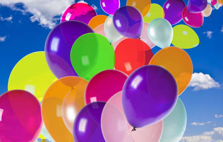 colorful balloons floating on a blue sky with clouds