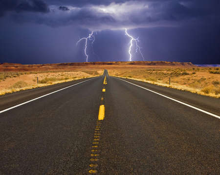 Two forks of bluish-white lightning strike on either side of a  highway at night