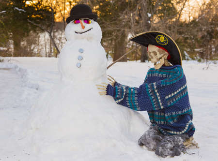 Skeleton building snowman in the snow 写真素材