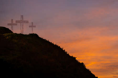 Three crosses on a hill at sunrise
