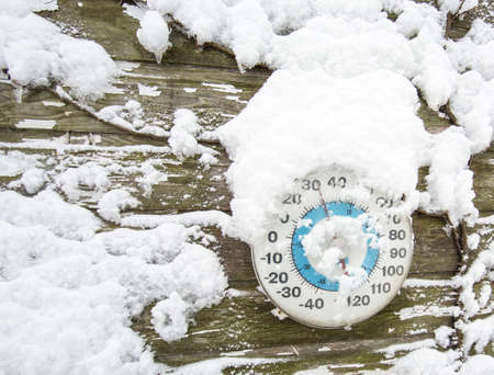 cold season: Thermometer in the snow on side of barn Stock Photo