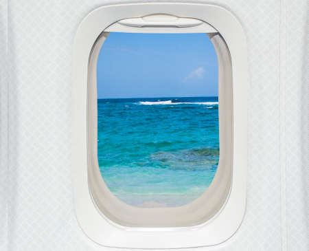 Aircraft window with beach and sky photo