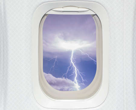 Aircraft window with view of lightning strike photo