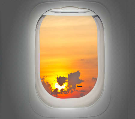 window view: Aircraft window with view of sunrise and plane Stock Photo