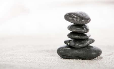 zen like: Stacked stones on sand in a Japanese ornamental or zen garden