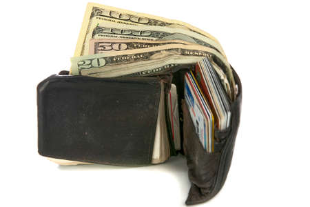 overfilled: Worn out wallet with cash and credit cards on white