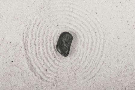 lines: Single stone on sand in a Japanese ornamental or zen garden