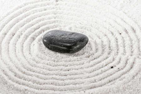 Single stone on sand in a Japanese ornamental or zen garden