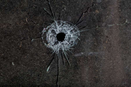 Bullet hole in glass on dirty grungy black background Stock Photo