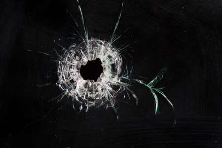 bullet holes in glass isolated on black Stock Photo - 36621272