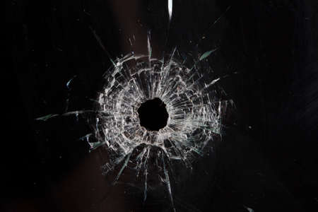 Einschusslöcher in Glas isoliert auf schwarz