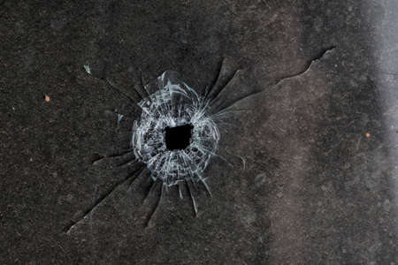 Bullet hole in glass on dirty grungy black background Stock Photo - 36621280