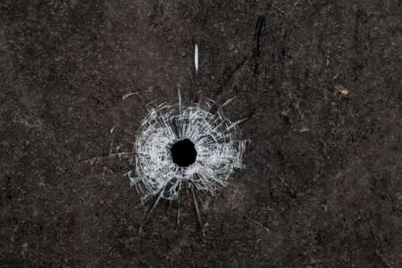 black hole: Bullet hole in glass on dirty grungy black background Stock Photo